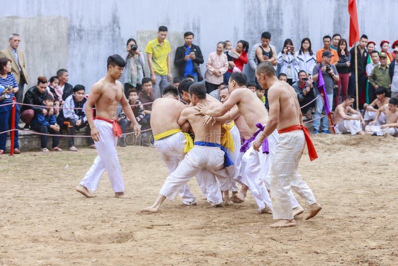 Niektóre młodzi człowiecy bawić się z drewnianą piłką w festiwalu księżycowym nowym roku przy Hanoi, Wietnam na Styczniu 27, 2016 zdjęcia stock