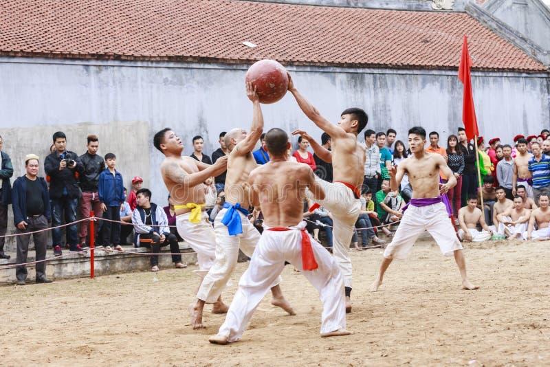Niektóre młodzi człowiecy bawić się z drewnianą piłką w festiwalu księżycowym nowym roku przy Hanoi, Wietnam na Styczniu 27, 2016 obraz royalty free