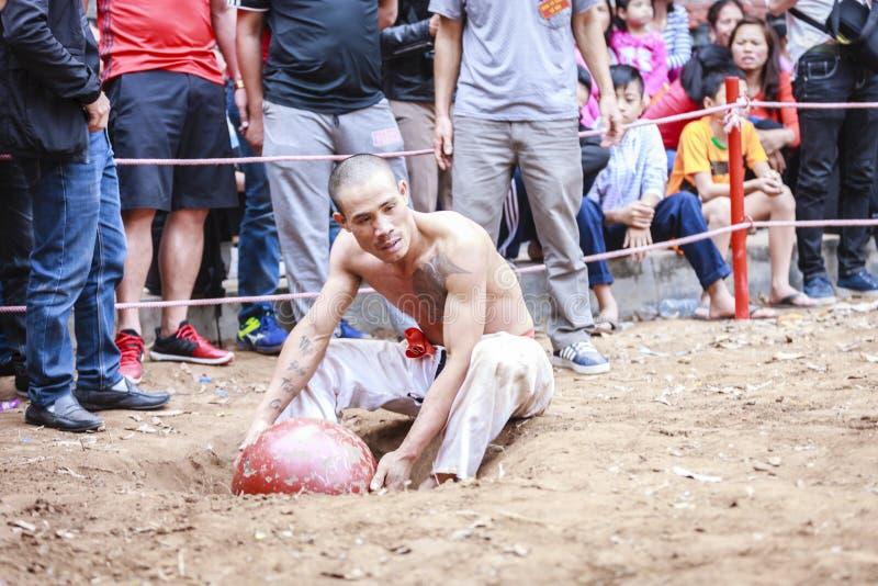 Niektóre młodzi człowiecy bawić się z drewnianą piłką w festiwalu księżycowym nowym roku przy Hanoi, Wietnam na Styczniu 27, 2016 zdjęcie royalty free