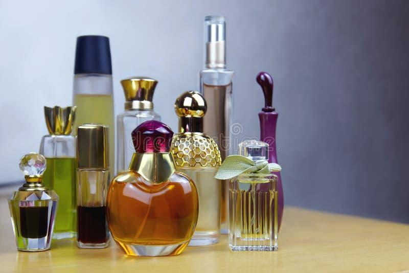 Niektóre rzędy pachnidło butelki na drewnianym stole Starzy roczników pachnidła fotografia stock