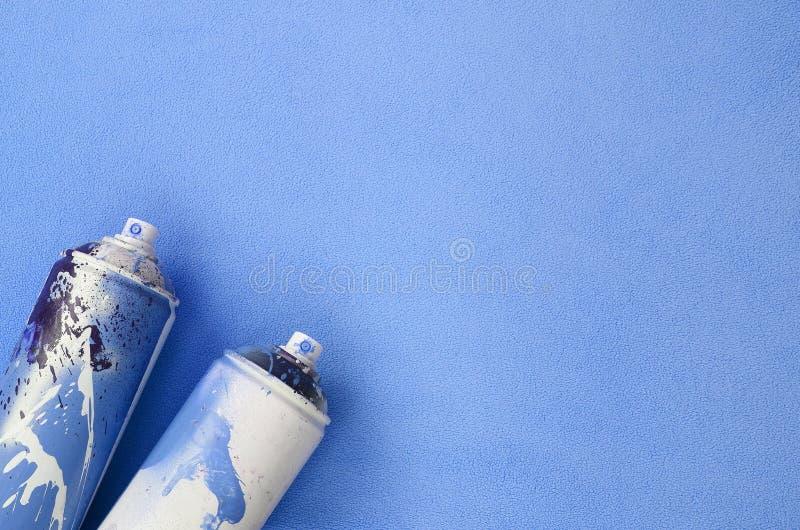Niektóre używać błękitne aerosolowej kiści puszki z farba kapinosami kłamają na koc miękka i owłosiona bława runo tkanina Klasycz zdjęcie royalty free