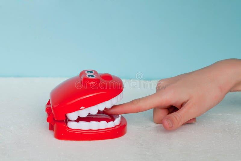 Niektóre zęby gryźć palec na błękitnym tle Palec w usta nie bagaż i to, wszystkie ręka gryźć daleko obrazy stock