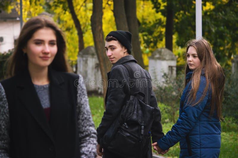 Nielojalny mężczyzna z jego dziewczyną i patrzeć zadziwiający przy inną uwodzicielską dziewczyną obrazy royalty free