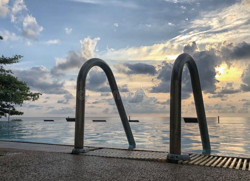 Niemand im Swimmingpool nahe bei dem Strand auf bewölktem Morgen des Sonnenaufgangs stockfotografie