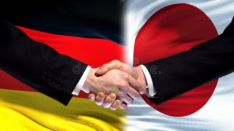 Niemcy i Japonia uścisk dłoni, międzynarodowi przyjaźni powiązania, chorągwiany tło zdjęcia royalty free
