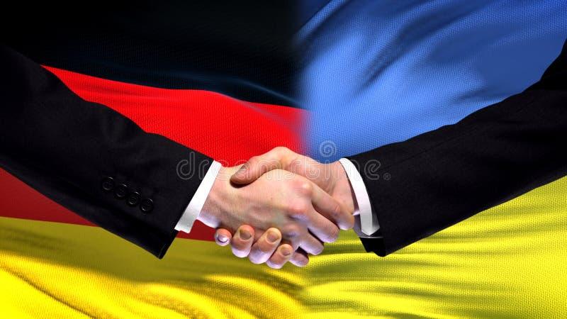 Niemcy i Ukraina uścisku dłoni przyjaźni międzynarodowi powiązania zaznaczają tło obrazy stock