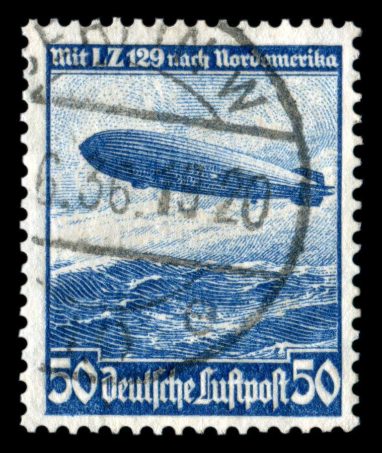 NIEMCY - OKO?O 1936: Niemiecki dziejowy znaczek: mesatlantica loty L Z 129 sterowiec ?Hindenburg ?nad Atlantyckim oceanem z obrazy royalty free