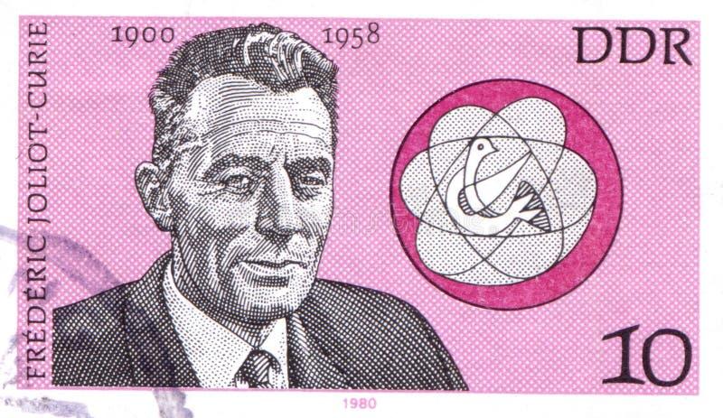 NIEMCY - OKOŁO 1980: znaczek drukujący w Niemcy pokazuje Frederic kiur, Francuski fizyk około 1980, zdjęcia stock