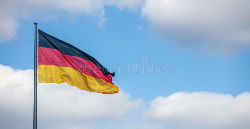 Niemiec chorągwiany falowanie na flagpole Chmurny niebieskiego nieba tło, copyspace, sztandar fotografia royalty free