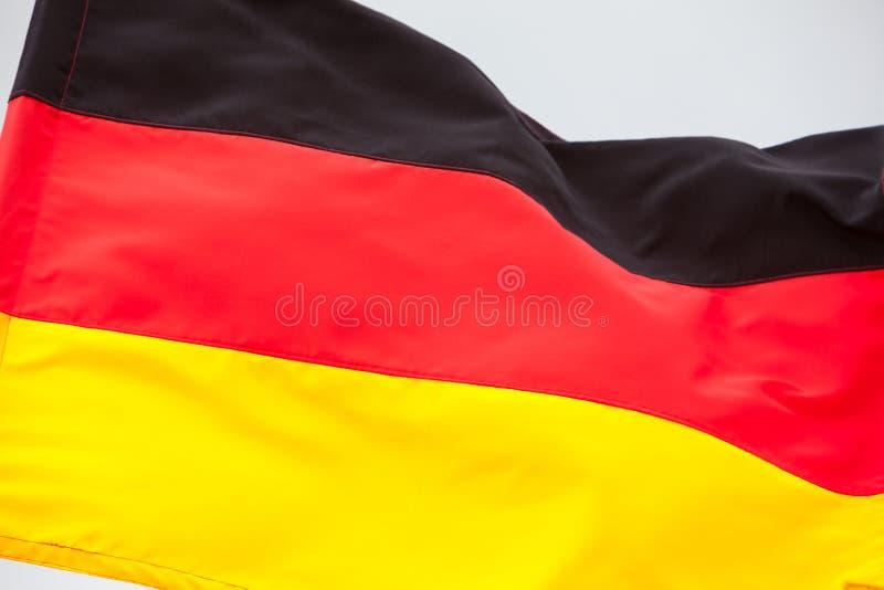 Niemiec chorągwiany falowanie na niebie zdjęcia stock