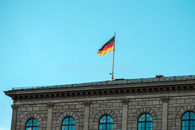 Niemiec chorągwiany falowanie na srebnym flagpole, budynek w Monachium zdjęcie royalty free