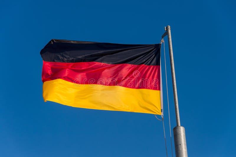 Niemiec chorągwiany falowanie przeciw niebieskiemu niebu fotografia stock