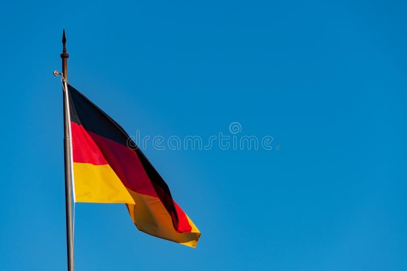 Niemiec chorągwiany falowanie w wiatrze przeciw jasnemu niebu fotografia stock