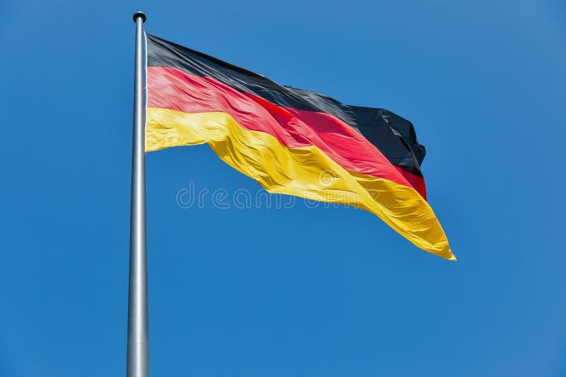 Niemiec flaga na flagstengi falowaniu przeciw jasnemu niebieskiemu niebu obrazy royalty free