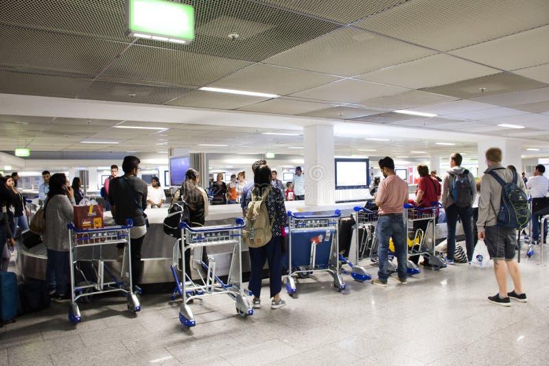 Niemiec i obcokrajowa podróżników czekać ludzie otrzymywają bagaż na carousel konwejerze przy Frankfurt lotniskiem międzynarodowy obrazy royalty free