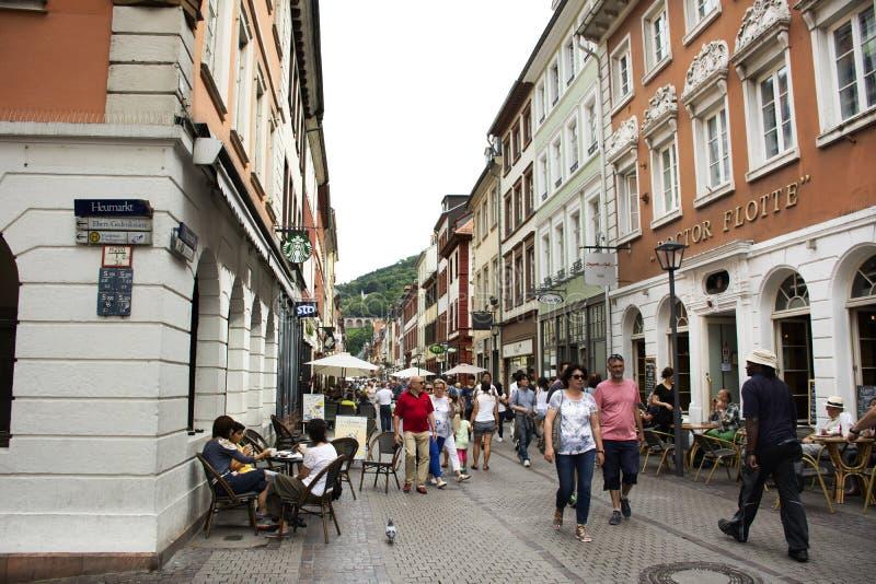 Niemieccy ludzie i cudzoziemscy podróżnicy chodzi wizytę i siedzą jedzą i piją przy Heidelberger starym miasteczkiem w Heidelberg obrazy royalty free
