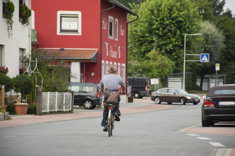 Niemieccy mężczyzn ludzie jechać na rowerze bicykl na Sandhausen ulicie w Heidelberg, Niemcy zdjęcia stock