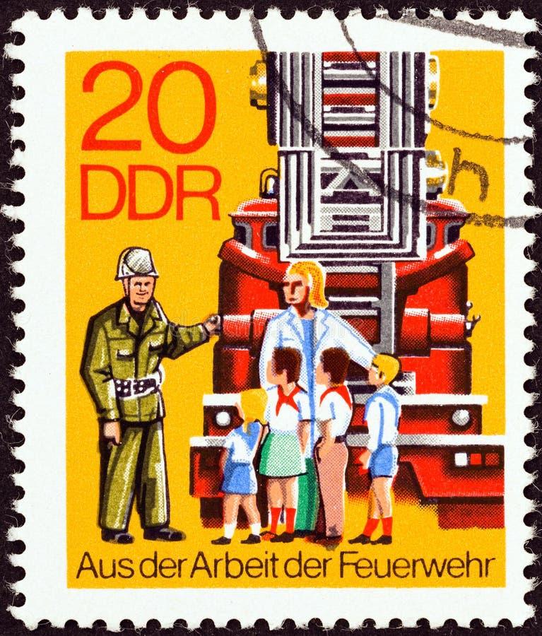 NIEMIECKA DEMOKRATYCZNA republika OKOŁO 1977 -: Znaczek drukujący w Niemcy pokazuje dzieci odwiedza jednostki straży pożarnej, ok zdjęcia royalty free