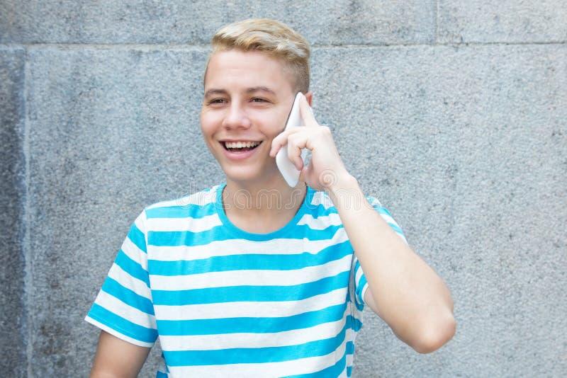Niemiecki młody dorosły mężczyzna opowiada przy wiszącą ozdobą z barwionym blondynem obraz stock