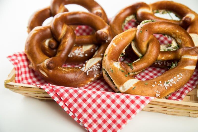 Niemiecki miękki Brezel precel z solą, szczypiorkami i masłem w chlebowym koszu, zdjęcie stock