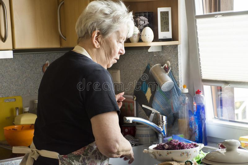 Niemieckie stare kobiety stoi lunch i gotuje przy kuchennym pokojem zdjęcie stock