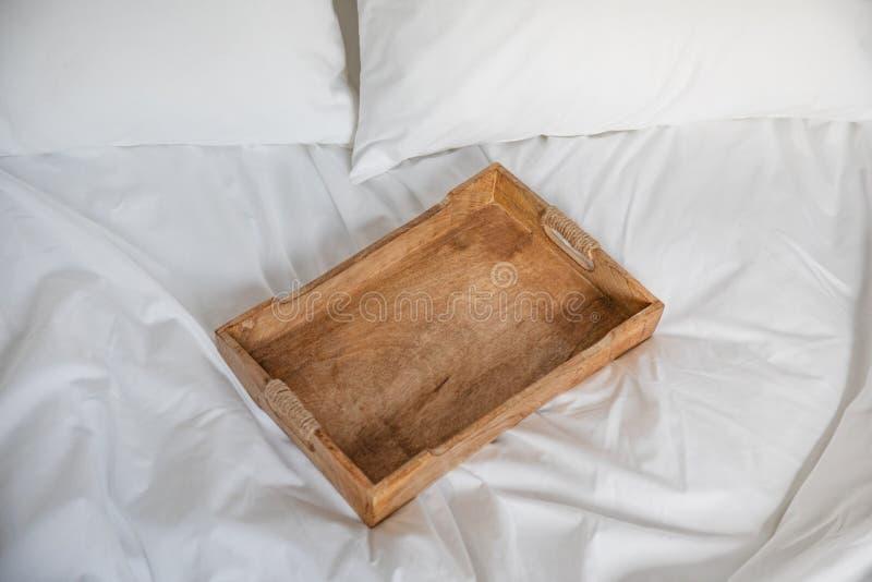 Nieociosana drewniana taca na białym łóżku Romantyczny śniadanie w łóżku zdjęcia stock