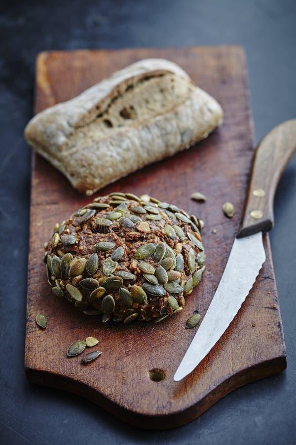 Nieociosane Chlebowe rolki na tnącej desce zdjęcia royalty free