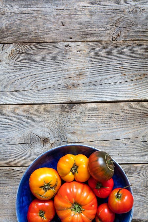 Nieociosani organicznie pomidory dla jarskiego menu nad rocznika drewnianym tłem zdjęcia stock