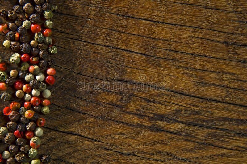 Nieociosany drewniany biurko i czerni stołowy tło z colour pieprzymy zdjęcie royalty free