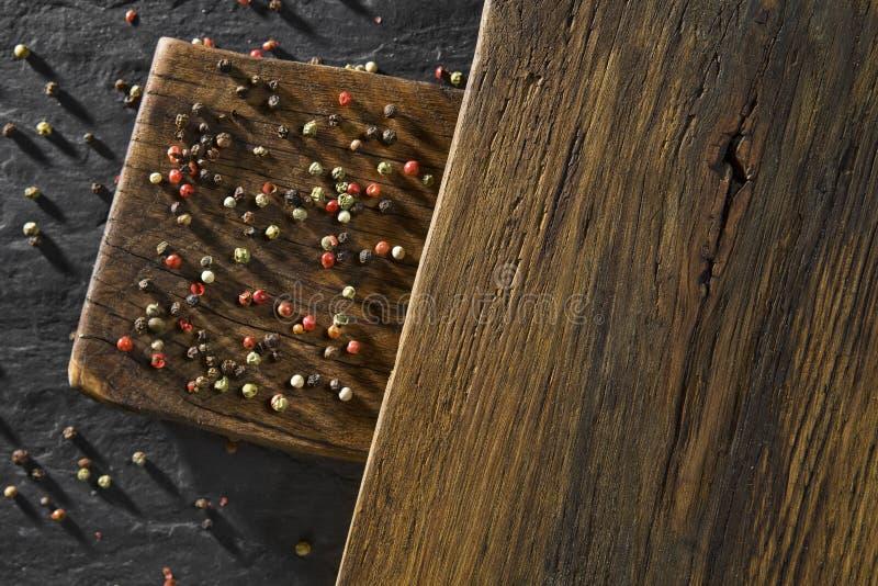 Nieociosany drewniany biurko i czerni stołowy tło z colour pieprzymy obraz royalty free