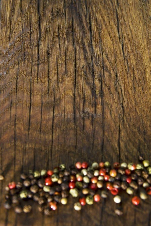 Nieociosany drewniany biurko i czerni stołowy tło z colour pieprzymy fotografia royalty free