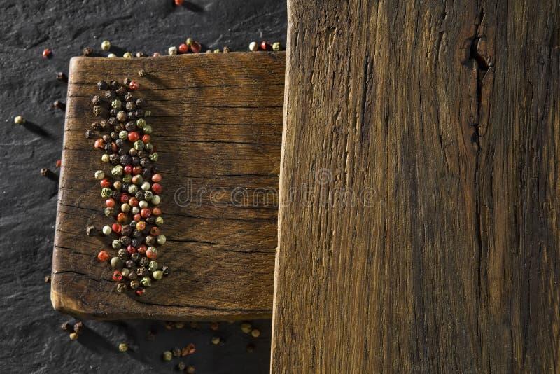 Nieociosany drewniany biurko i czerni stołowy tło z colour pieprzymy zdjęcia royalty free