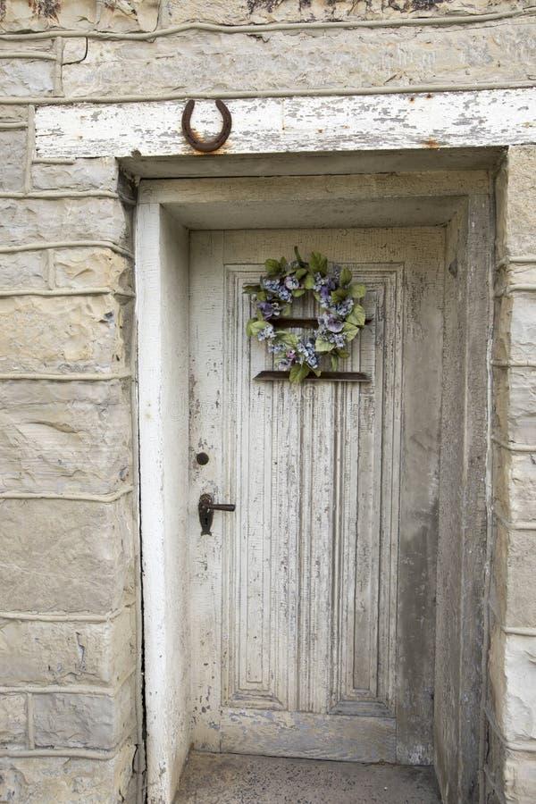 Nieociosany drewniany drzwi na kamiennej ścianie obrazy royalty free