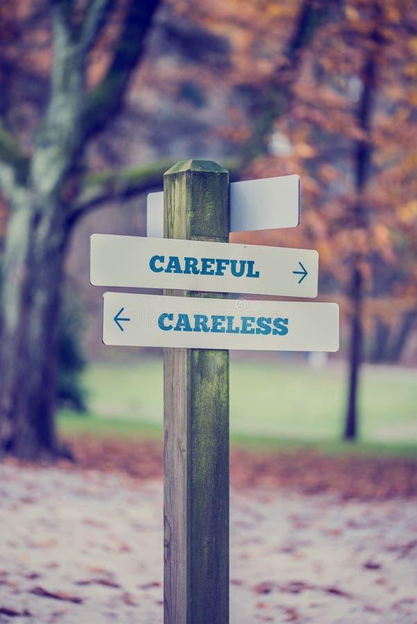 Nieociosany drewniany podpisuje wewnątrz jesień parka z słowami Ostrożnymi - Ca obraz stock