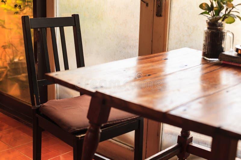 Nieociosany drewniany stół i krzesła z ciepłym naturalnego światła położeniem iluminującym przez drzwiowego szklanego okno Salowa obrazy royalty free