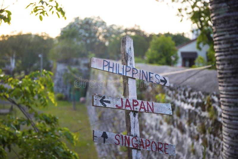 Nieociosany drewniany znak uliczny dla Filipiny, Japonia i Singapur, Fortu San Pedro ściany widok obraz royalty free