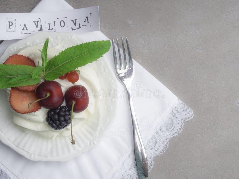 Nieociosany Pavlova tort z świeżymi truskawkami, cherrys, blackberrys, mennicą i batożącą śmietanką nad betonowym tłem, obraz stock