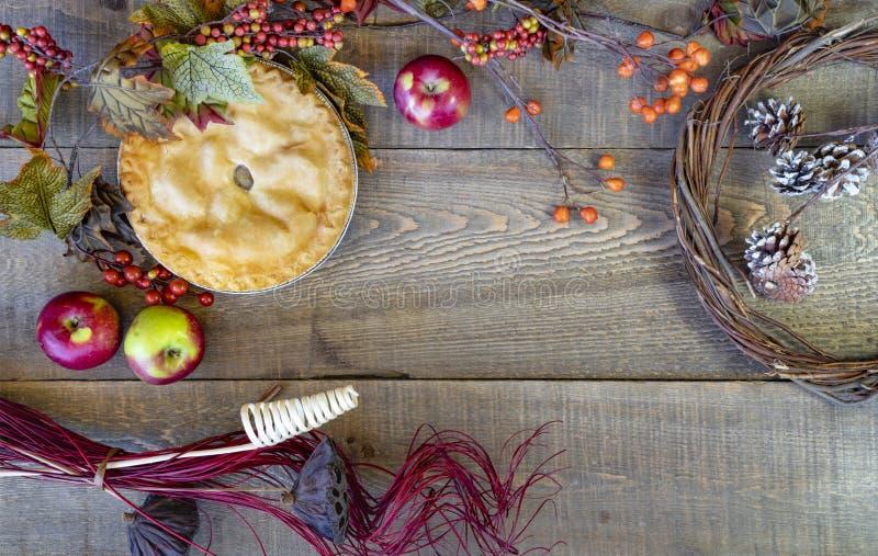 Nieociosany spadku wystrój i jabłczany kulebiak na drewnianym deski tle zdjęcia stock
