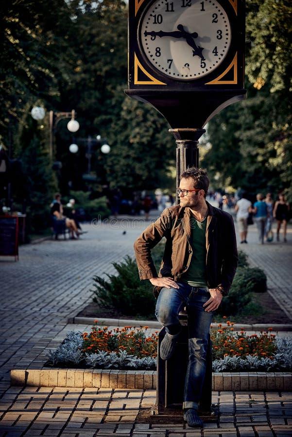 Nieogolony rozkudłany młody człowiek blisko ulicznego zegaru w mieście obraz royalty free