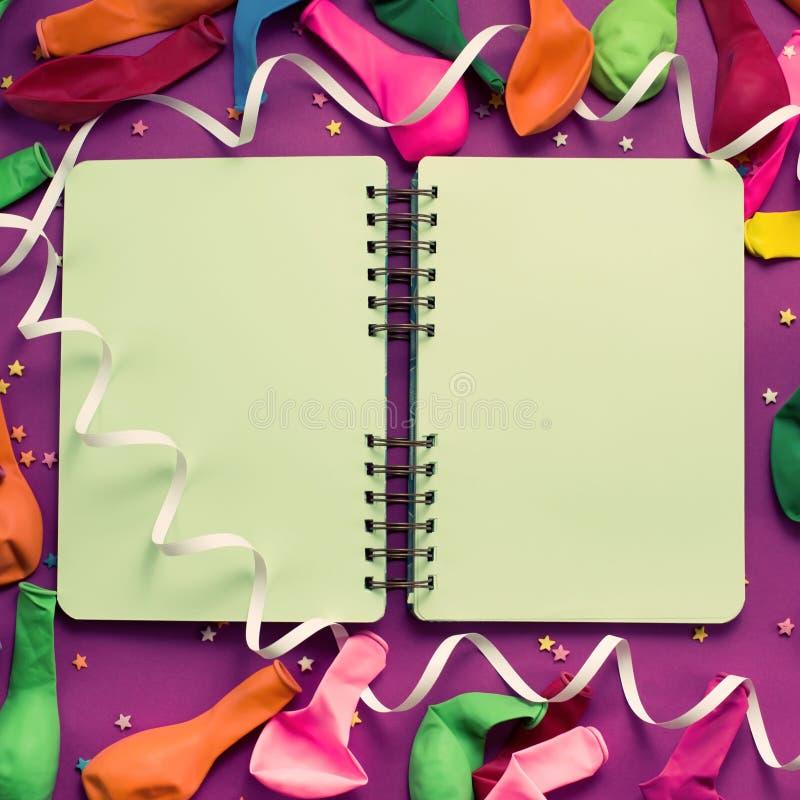 Nieosłonięty notatnik dla rejestrów na purpurowy świąteczny tło barwiącej balonów streamers Odgórnego widoku tła kopii świąteczne obraz royalty free