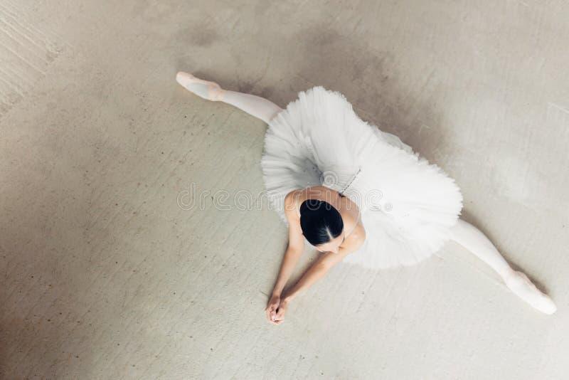Niepłonny choreograf siedzi na podłodze z nadużytymi nogami obraz royalty free