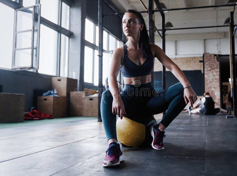 Niepłonny żeński trening sprawności fizycznej klub, siedzi gym uśmiechu kamerę, wyciera pot z czoła, chudy medycyny piłki crossfi fotografia royalty free