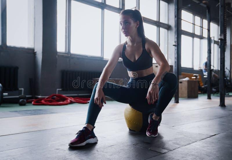 Niepłonny żeński trening sprawności fizycznej klub, siedzi gym uśmiechu kamerę, wyciera pot z czoła, chudy medycyny piłki crossfi obrazy stock