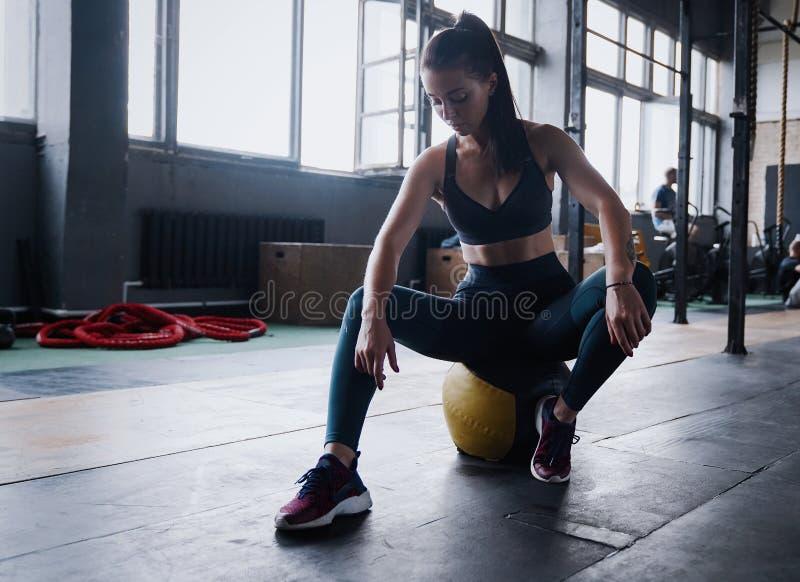 Niepłonny żeński trening sprawności fizycznej klub, siedzi gym uśmiechu kamerę, wyciera pot z czoła, chudy medycyny piłki crossfi zdjęcie stock
