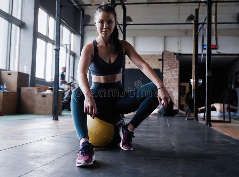 Niepłonny żeński trening sprawności fizycznej klub, siedzi gym uśmiechu kamerę, wyciera pot z czoła, chudy medycyny piłki crossfi obraz stock