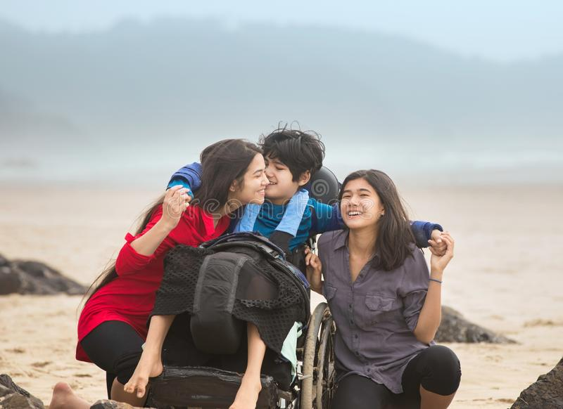 Niepełnosprawny brat ściska stare siostry na plaży w wózku inwalidzkim obrazy stock