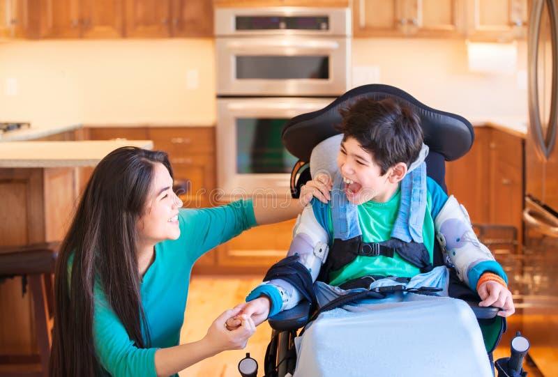 Niepełnosprawna chłopiec śmia się z nastoletnią siostrą w kuchni w wózku inwalidzkim zdjęcie stock