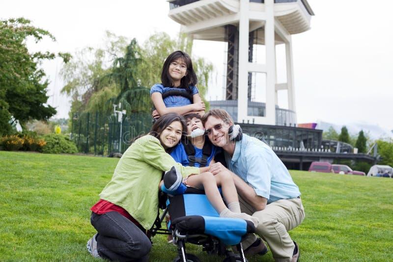 Niepełnosprawna chłopiec w wózek inwalidzki otaczającym rodziną fotografia stock