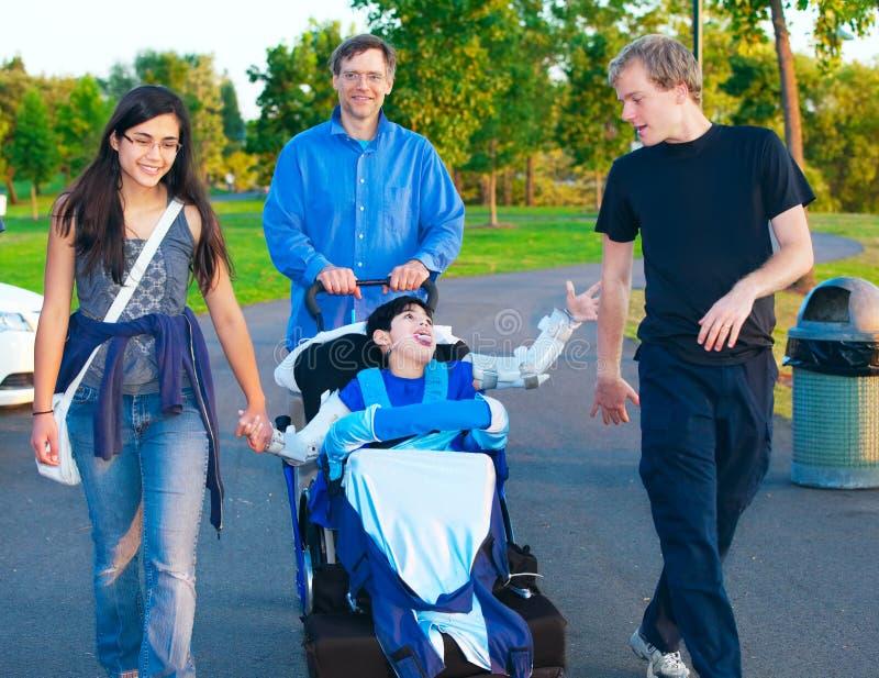 Niepełnosprawna chłopiec w wózka inwalidzkiego odprowadzeniu przy parkiem wraz z rodziną zdjęcia stock