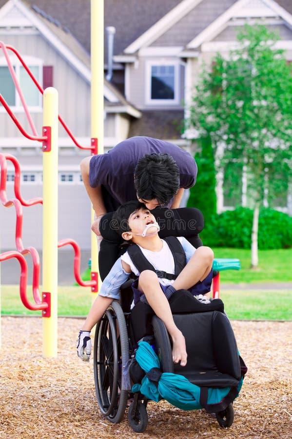 Niepełnosprawna chłopiec w wózku inwalidzkim z bratem przy parkiem obrazy stock